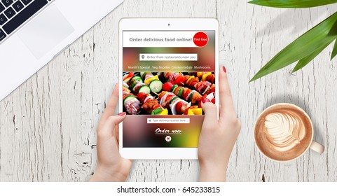 Female hands using tablet for food ordering online, on the table surrounded with coffee, plant and laptop