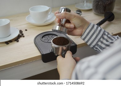 female hands using tamper into portafilter