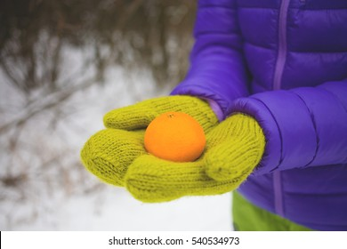 female hands in warm green mittens holding a Mandarin on a background of snow.