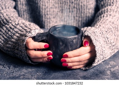 Female hands warm up hands on a hot cup