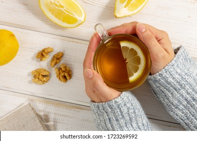 Female hands in warm sweater holding cup of tea with lemon on white wooden table. Alternative medicine concept. Safe treatment. Top view