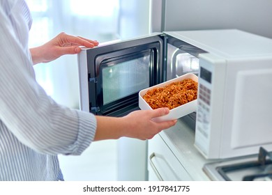 Female hands warming up a container of food in the modern microwave oven for snack lunch at home