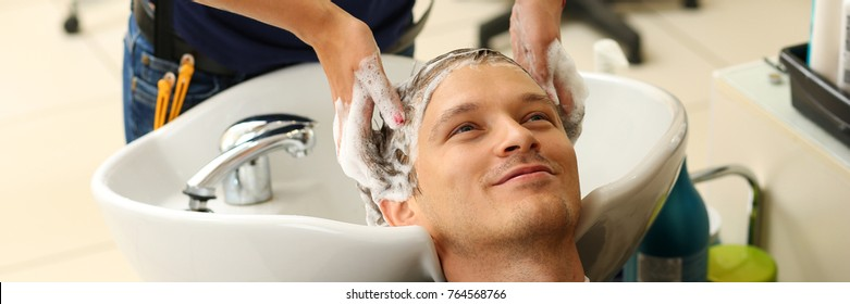 Female hands washing hair to handsome smiling man at hairdresser with shampoo before haircut. Keratin restoration, latest trend, fresh idea, haircut picking, instrument store concept. Letterbox view