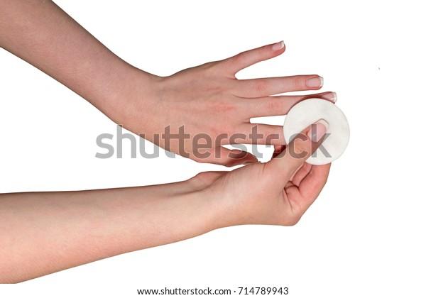 白い背景に女性の手が綿の円盤でマニキュアを洗い落としている