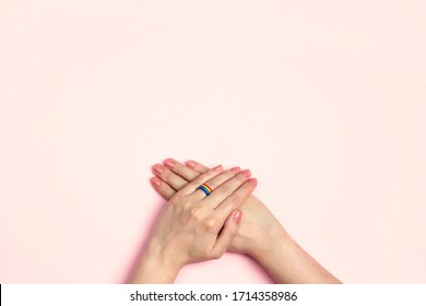 Female hands with a wedding ring from a rainbow ribbon on a pink background. Lesbian marriage proposal. LGBT family, pride month.