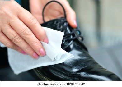 female hands with wet wipe stain excretion from leather shoes