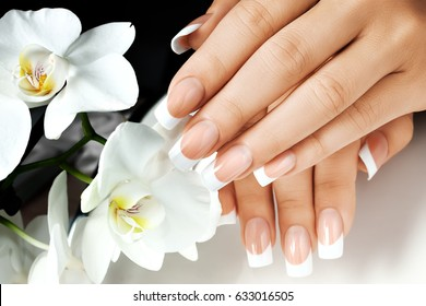 Female hands with white nails on background of white flowers.