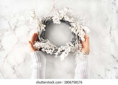 Female hands with white warm sleaves holding a Christmas wreath against marmor background