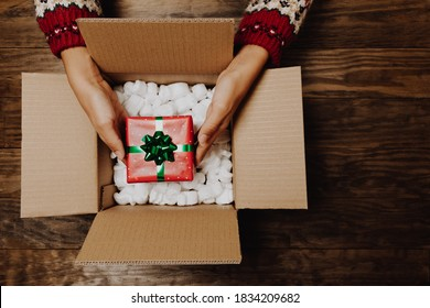 Female hands with a winter sweater packing or unpacking a Christmas gift from a cardboard box on a rustic wooden table. Christmas home delivery or shipping concept. Top view