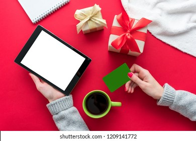 Female hands, woman holding a tablet pc and Business card. Cup of coffee or tea, red table, gifts boxes for the holidays, background with copy space for advertisement, top view