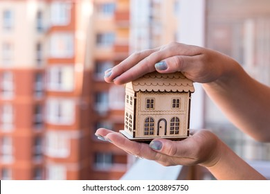 Female hands with wooden house model on construction site background