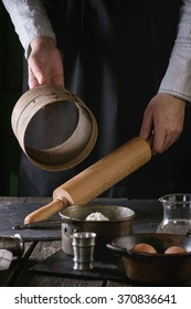 Female hands with wooden rolling-pin and sieve ready to cook the dough in dark rustic kitchen. Vintage kitchenware with flour, water and eggs at foreground.