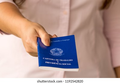 """Female hands of a worker holding a portfolio work permit of the Ministry of Labor and Social Security of Brazil. (Translation: """"Work Permit, Ministry of Labor and Social Security of Brazil CTPS""""). New"""