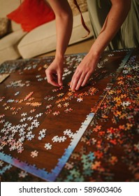 Female hands working on a large, complicated jigsaw puzzle, laid out on a wooden coffee table. Organising by colour. Puzzle solving.
