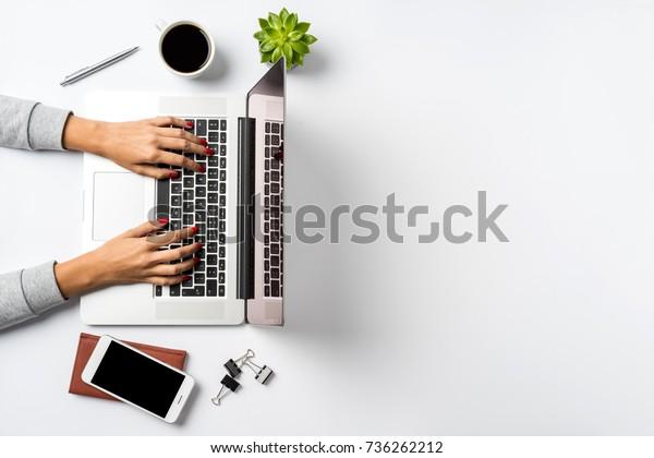 Weibliche Hände, die auf einem modernen Laptop arbeiten. Office-Desktop auf weißem Hintergrund