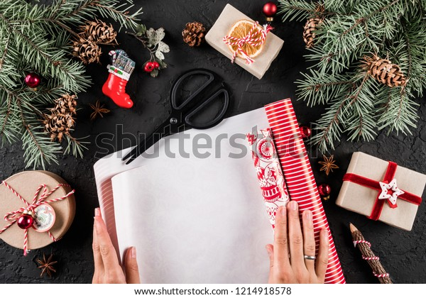 Female hands wrapping a Christmas gift on holiday wrapping on black background with fir branches, red decorations. Xmas and Happy New Year card. Flat lay, top view