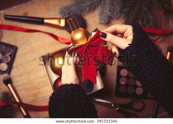 Female hands wrapping cosmetics in christmas gifts on wood background
