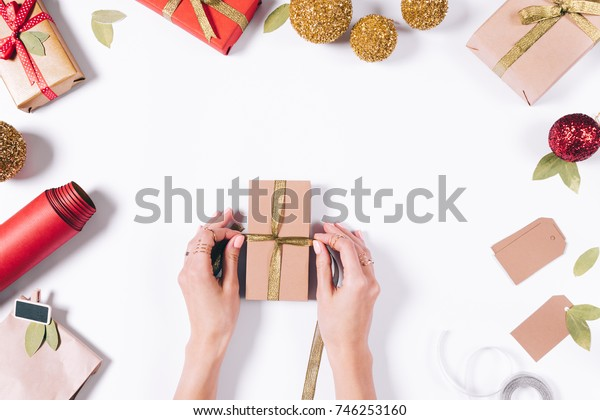 Female hands wrapping a gift for the new year on a white background top view