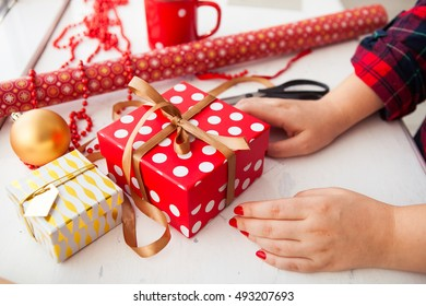 Female hands wrapping xmas gifts into paper and tying them up with gold threads
