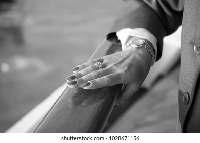 Female hands and wrist-watch with red manicure and golden ring on finger with diamonds near water
