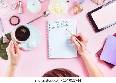 Female hands write To do list on the pink background with cosmetics, coffee cup, notebooks, tablet with blank screen. Beauty blog concept. Top view feminine office table desk. Freelancer working place