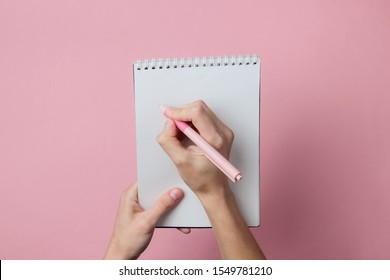 Female hands write with a pen in a notebook on a pink background. Girl's diary. Pastel color trend