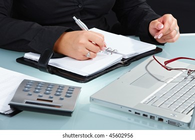 Female hands writing into notebook.