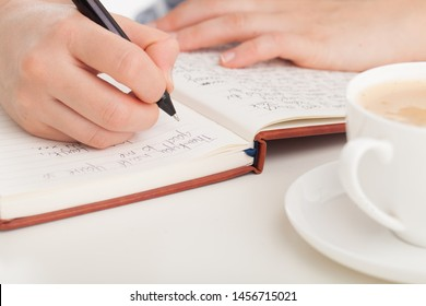 Female hands writing in leather bound journal or diary with coffee