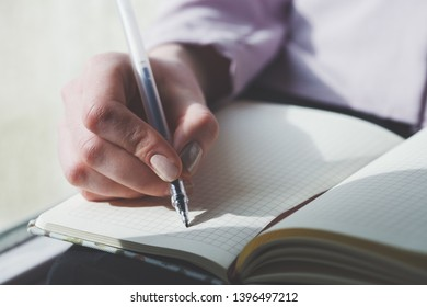 female hands writing notes on notebook with pen