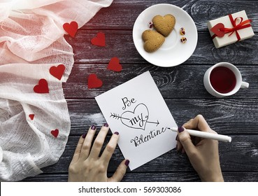"""Female hands writing White ink Pen a  Valentine's day letter with gentle message """"Be my Valentine"""" with gift box and cup of fruit tea, rose petals and saucer with sweets.. Flat lay. Ray of sunshine."""