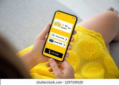 female hands in yellow dress holding phone with app call taxi on the screen