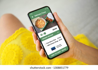 female hands in yellow dress holding phone with app delivery food on the screen