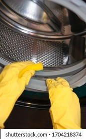 Female hands in yellow latex gloves for cleaning with a sponge wash the dirt around the drum of a black washing machine.
