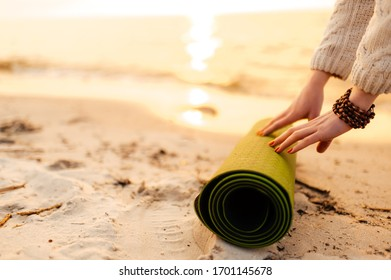 Female hands and yoga mat in the sand on the beach at sunset, close-up