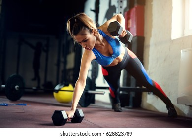 Female hard work at gym with dumbbells push ups. Strong woman at gym.