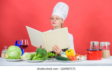 Female in hat and apron knows everything about culinary arts. Culinary expert. Woman chef cooking healthy food. Girl read book top best culinary recipes. Traditional cuisine. Culinary school concept.
