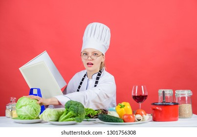 Female in hat and apron knows everything about culinary arts. Culinary expert. Woman chef cooking healthy food. Girl read book best culinary recipes. Culinary education concept. Improve cooking skill.
