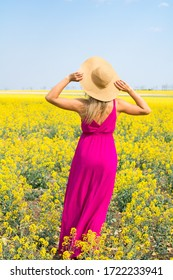 female in hat and magenta dress is standing in the yellow field and admires of the view. view from the back