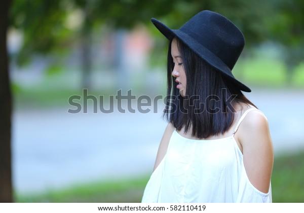 female hat nature summer sun sunset looks pleased. azitka woman black hair dancing around trees.