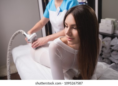 Female having procedure of massage on legs in apparatus cosmetology clinic. Woman in special white suit getting anti cellulite massage in a spa salon. LPG treatment