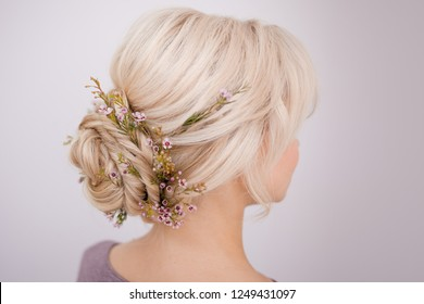 Female head back view. Make an elegant hairstyle with petals. Hairstyle beam on blonde hair