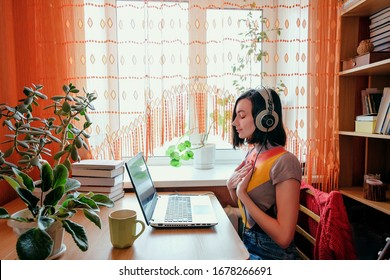 Female in headphones sits at front of laptop and breathing. Online audio meditation concept