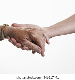 Female health care worker supports the hand of a senior female patient
