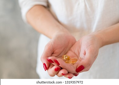 Female health and vitamin deficiency. Woman holding fish oil supplements in hands.