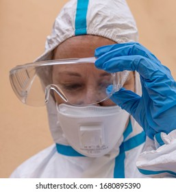 Female health worker takes off protective glasses exhausted from fatigue after battling the terrible Coronavirus Covid-19 in Italy