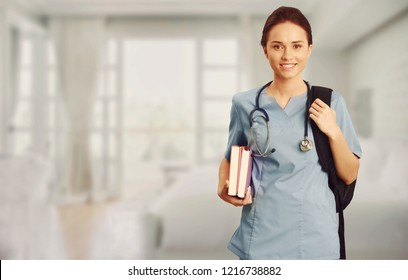 Female healthcare worker wearing scrubs and carrying