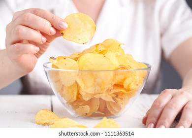 Female with heap of potato chips in big dish