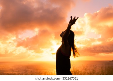 Female with her hand up in the air looking into the sky.