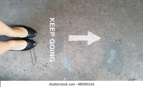Female high heels on the cement road with a drawing direction arrow with the word keep going