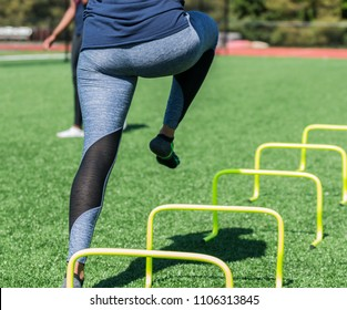 A female high school athlete performs running drills over yellow mini banana hurdles on a turf field with no shoes on, only socks in blue spandex.